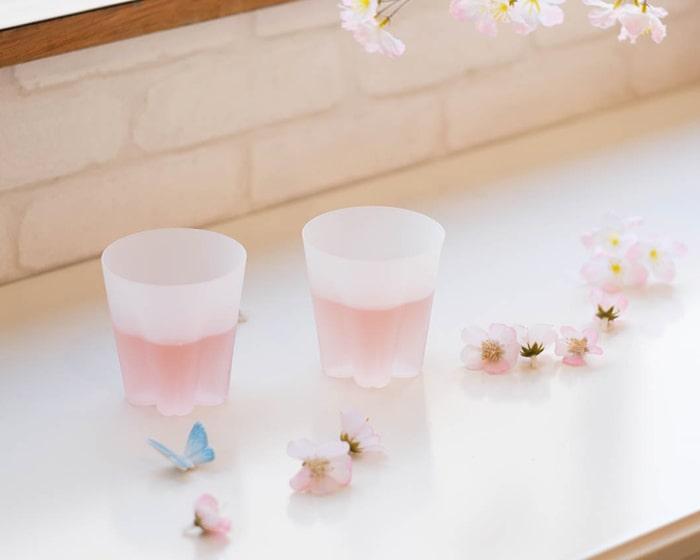テーブルに飲み物の入ったサクラサクグラスと桜の花びらが綺麗に散りばめられている