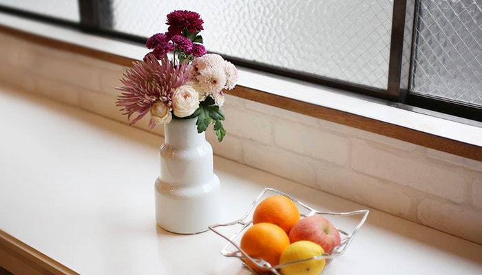 1616/arita japanの花瓶に花が活けてあり、手前にはフルーツの入ったKAGO