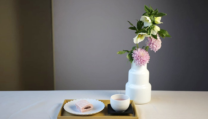 Flower vase on the right side with beautiful flowers, and Japanese confectionery and Japanese tea on a tray