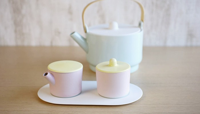 There is a sugar and creamer set of light yellow and pink. Behind it, there is a teapot