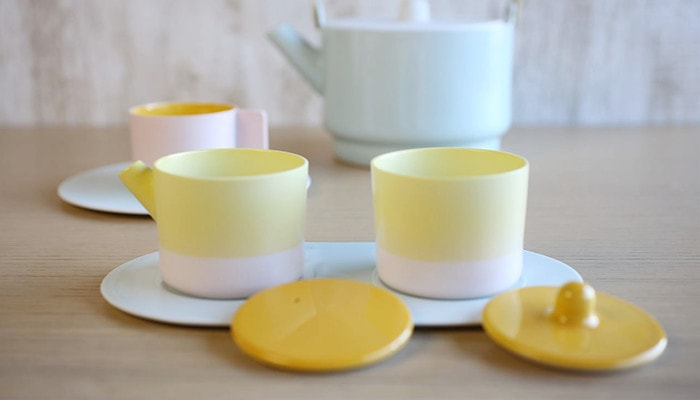 Yellow sugar and creamer set. Behind it, there are a teapot and a pair of cup and saucer
