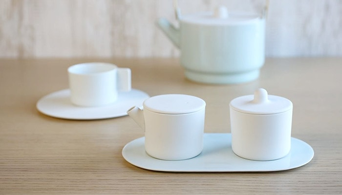 White sugar and creamer set.Behind it, there are a teapot and a pair of cupa and saucer