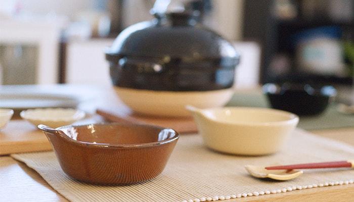 アグラとんすいや土鍋、箸などがテーブルに並んでいる