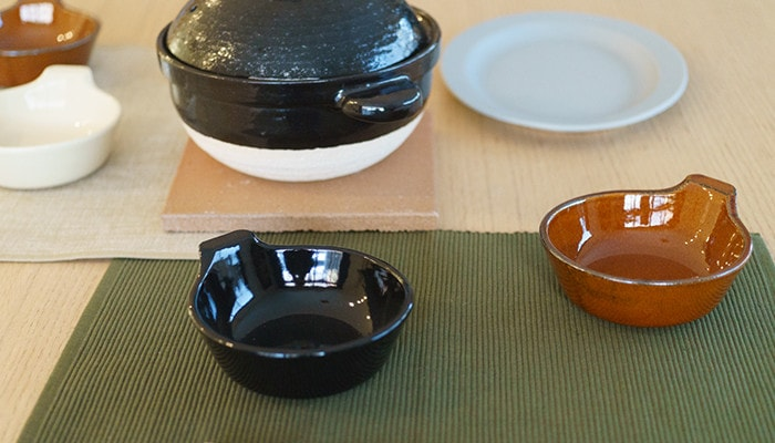 アグラとんすいや土鍋、お皿がテーブルに並んでいる