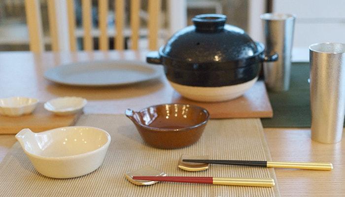 食卓にとんすいや箸、土鍋やビアカップなどが並んでいる