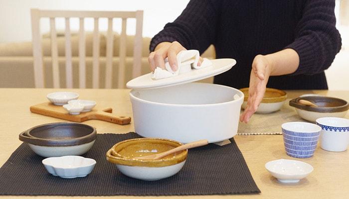 テーブルにとんすいや豆皿など鍋のセットがあり、女性が鍋の蓋を持っている様子
