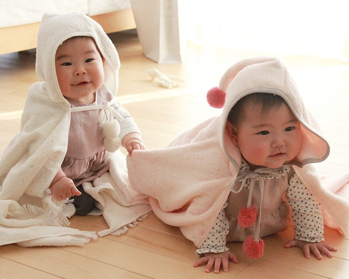 2 babies are playing while wearing baby ponchos