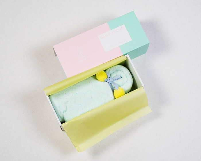 Mint baby poncho within its exclusive box