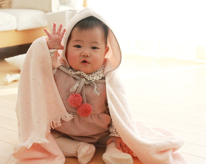 A baby raises right hand with wearing BAB PONCHO