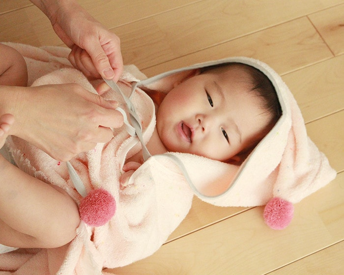A baby wears BAB PONCHO after a bath