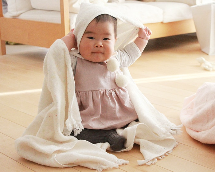 A baby is wrapped with hooded towel from amabro