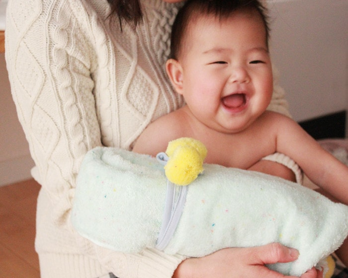 A baby is smiling on the lap of his mother with baby poncho
