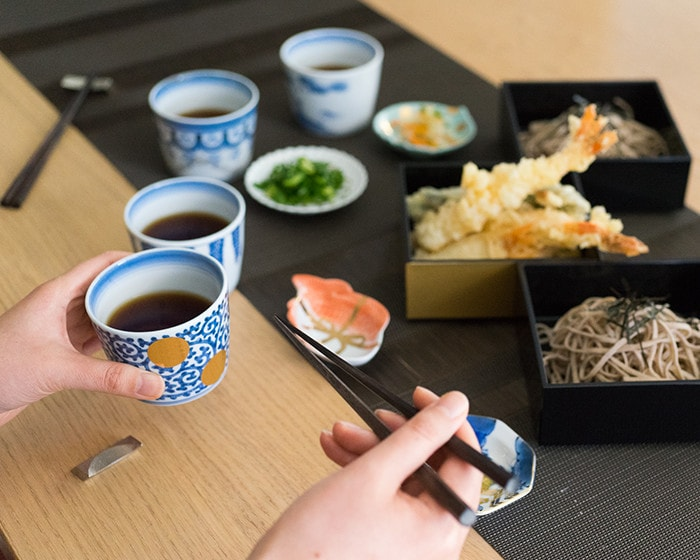 A woman is eating soba with blue and white Arita soba cups