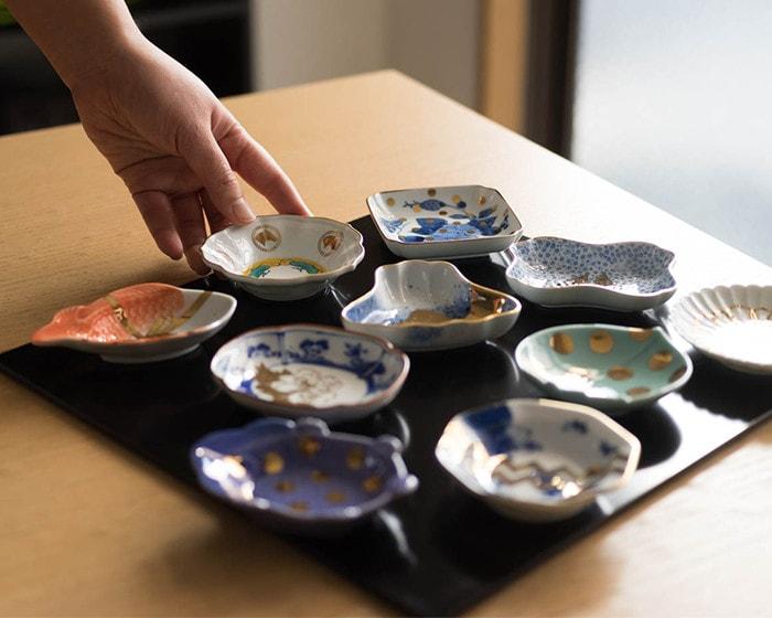折敷の上にamabroの豆皿がいくつも並んでいて内ひとつに女性が手を添えている