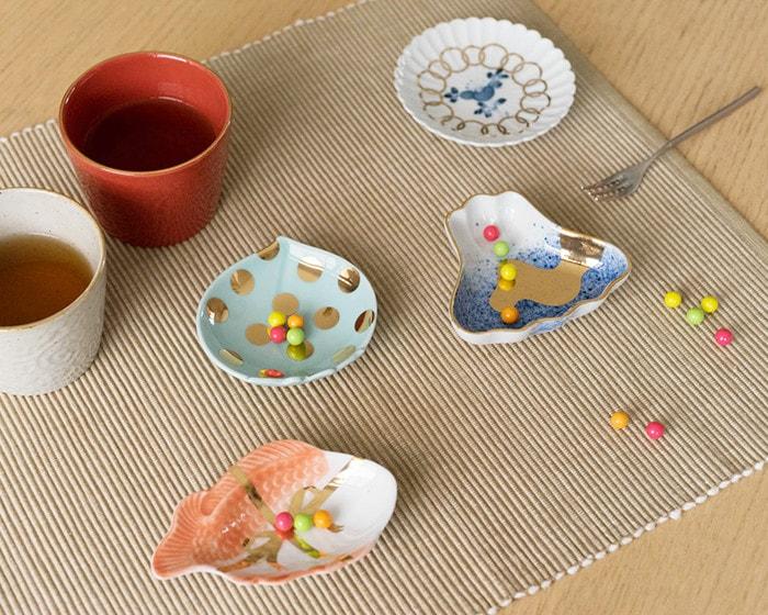 テーブルに駄菓子の乗ったamabroの豆皿やお茶の入ったそば猪口が並んでいる
