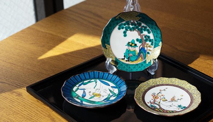 折敷の上に九谷焼のムーミンシリーズのお皿が3枚並んでいる