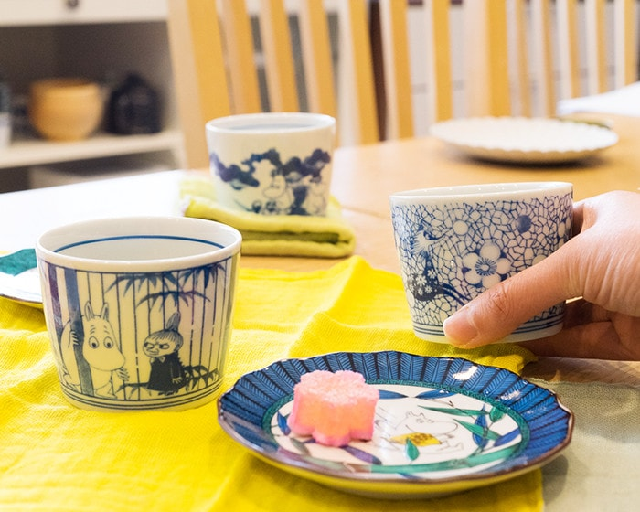 Sometsuke choko cups on the table and a woman has a cup