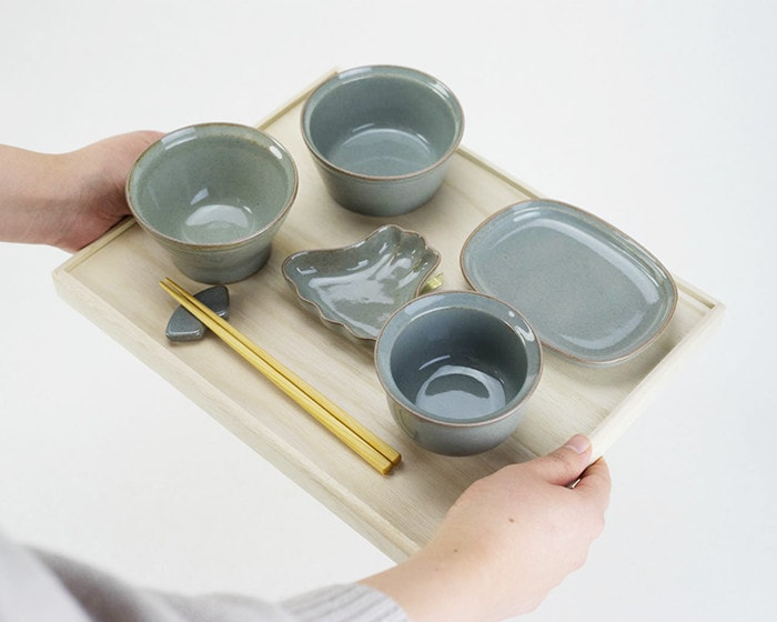 A woman serves a tableware set of OKUIZOME