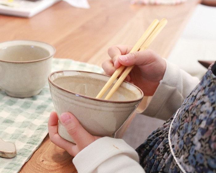 A child holds a rice bowl and tries to use chopsticks