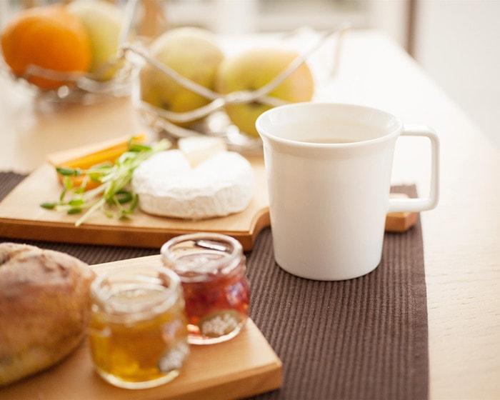 食卓にはチーズやパンが並んでいて、カップは1616arita/japanのTY白色のマグカップを使っている