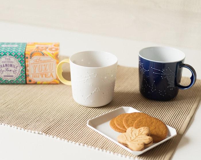 星座マグの白色と瑠璃色が並んでいて手前にはクッキーが乗った小さな白いプレート