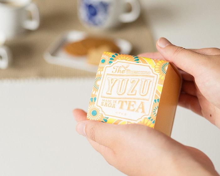 うれしの紅茶YUZUのボックスを女性が手に持っている