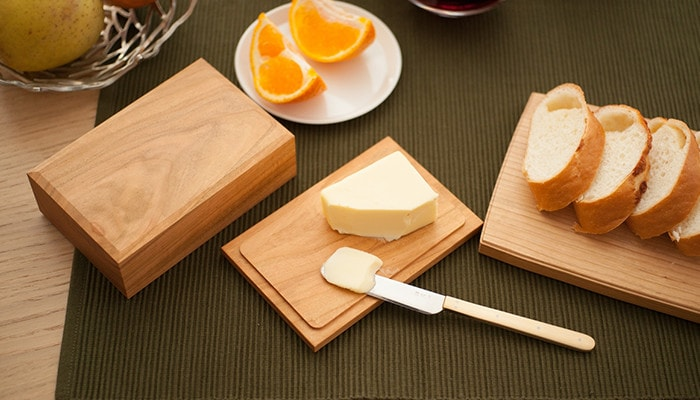 テーブルにバターケースに乗ったバターやチーズボードに乗ったパンが並んでいる様子