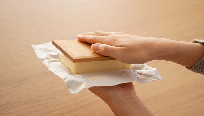 バターの上に底板を被せて押さえている様子