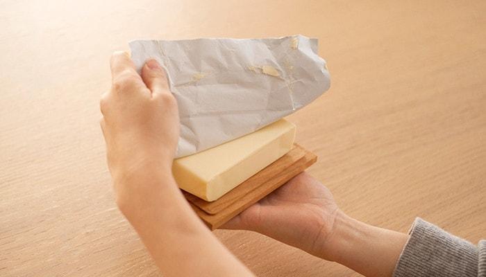 底板の上にバターを乗せて包み紙をはがしている様子