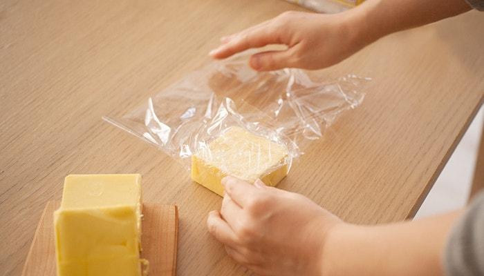 切り分けたバターをラップで包んでいる様子