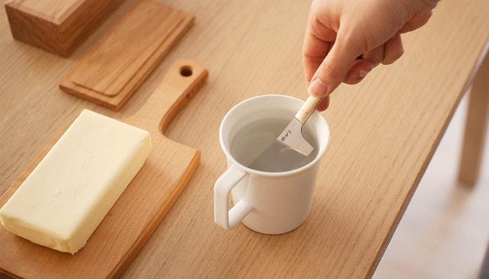 マグカップに入ったお湯で、チーズナイフを温めている様子