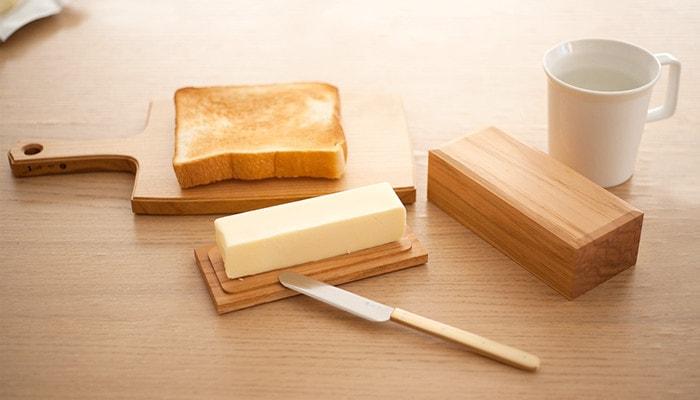 チーズボードに乗った焼いた食パンやバターケースの底板乗ったバターなどがテーブルに並んでいる様子