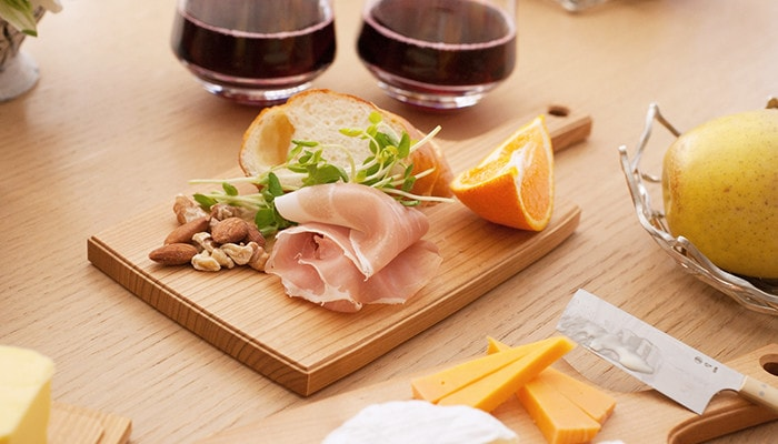 Home party with ham, nuts, and bread on the wooden cheese board