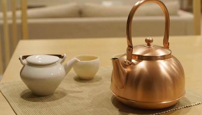 Copper tea kettle of azmaya and kyusu and yunomi of ceramic japan on the table