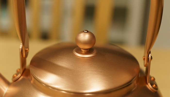 Cute spheric knob of the copper tea kettle