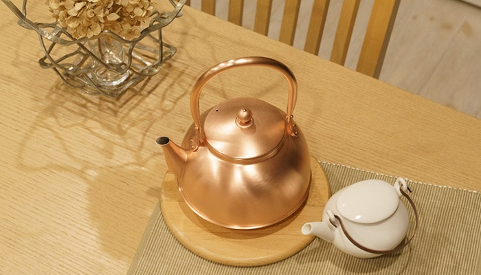 テーブルに置かれた銅のやかんや急須、能作のKAGOを上から見た様子