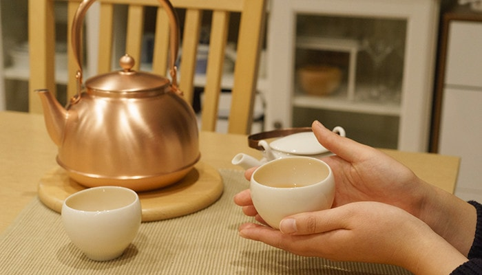 A woman drinks tea with yunomi. Copper tea kettle is on the table