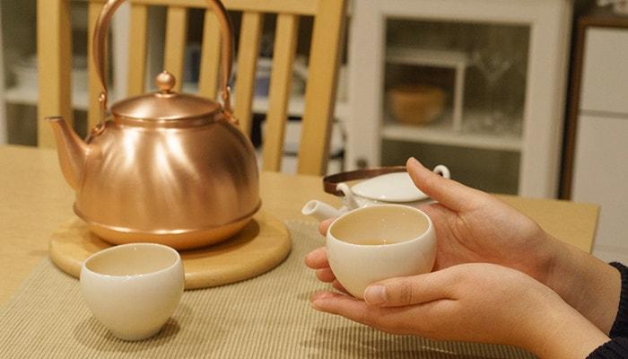女性がお茶の入った湯吞みを持っている様子。テーブルには東屋のやかんや湯呑みが置いてある