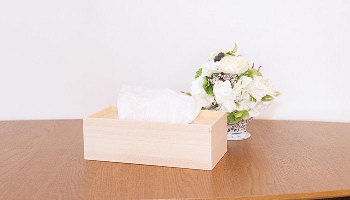 テーブルに東屋の木製ティッシュケースと花が置かれている