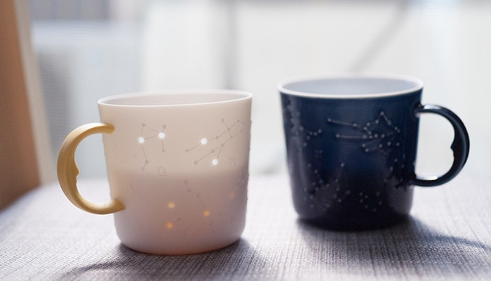 Yellow and azure blue constellation mugs with tea. We can see the color of tea within the yellow mug
