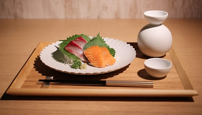 Sashimi with Japanese sake in Shuki daruma