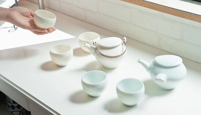 蒼爽シリーズの急須や土瓶・湯のみが並んでいる。女性が湯のみを持っている