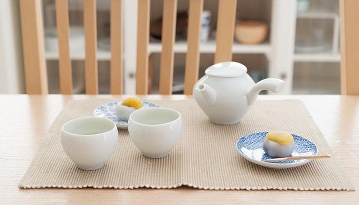 テーブルに蒼爽シリーズの青白磁のセットと和菓子の乗った小皿が並んでいる