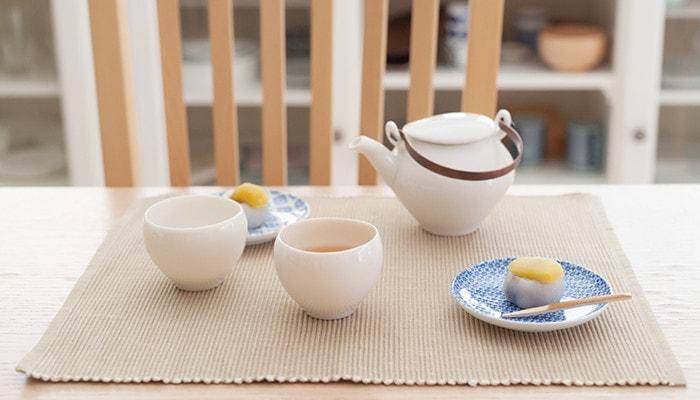 テーブルに蒼爽シリーズの黄磁のセットと和菓子の乗った小皿が並んでいる