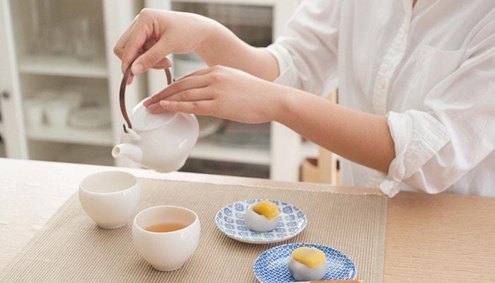 女性が黄磁セットの土瓶でお茶を入れている様子