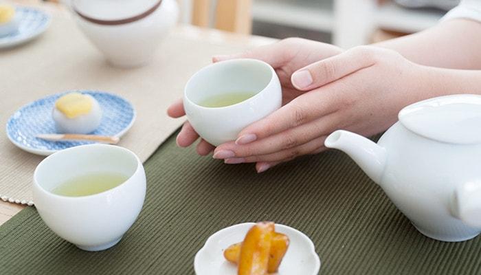 女性がお茶の入ったセラミックジャパンの蒼爽シリーズ湯呑みを持っている