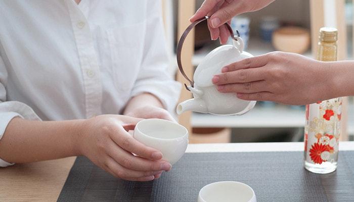 セラミックジャパンの黄磁の土瓶でお酒を注いでいる様子