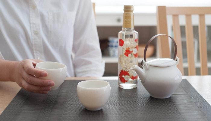テーブルにセラミックジャパンの黄磁セットとお酒が置かれていて、女性が湯呑みを持っている様子