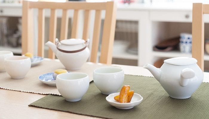 テーブルにセラミックジャパンの蒼爽シリーズの急須セットや和菓子の乗った小皿が並んでいる