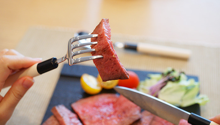 A woman takes cut roast beef with unique fork of Japanese silverware set